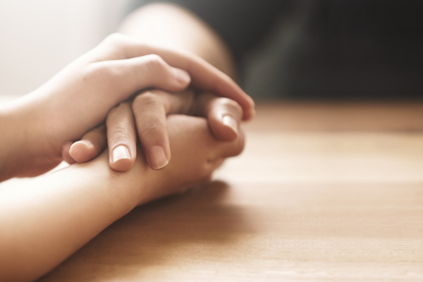 2 Hände umschliessen eine Hand des Trauernden