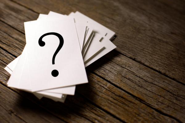 Stapel von weissen Karten mit aufgedrucktem Fragezeichen auf dunklem Holzboden