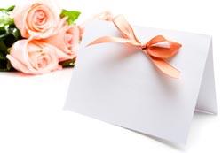 Weisse karte mit rosa Schlaufe und rosa Rosen dahinter